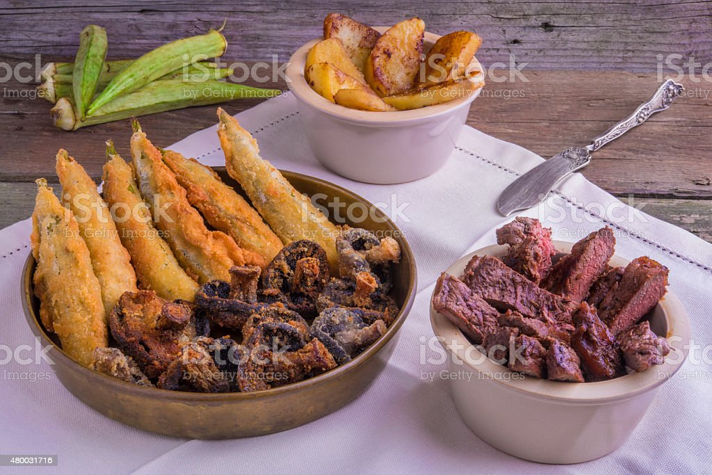 Cajun grilled entrecote, deep fried okra, mushrooms and yams stock photo