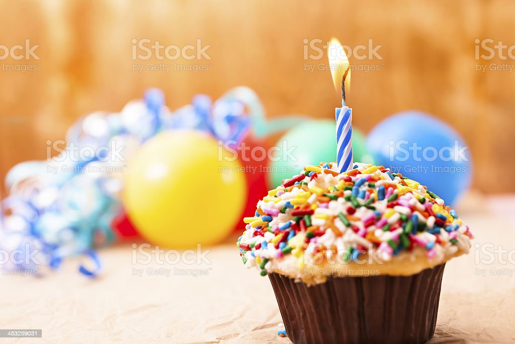 Cake and Candles: Birthday cupcake, one burning candles. Sprinkles. Balloons. royalty-free stock photo