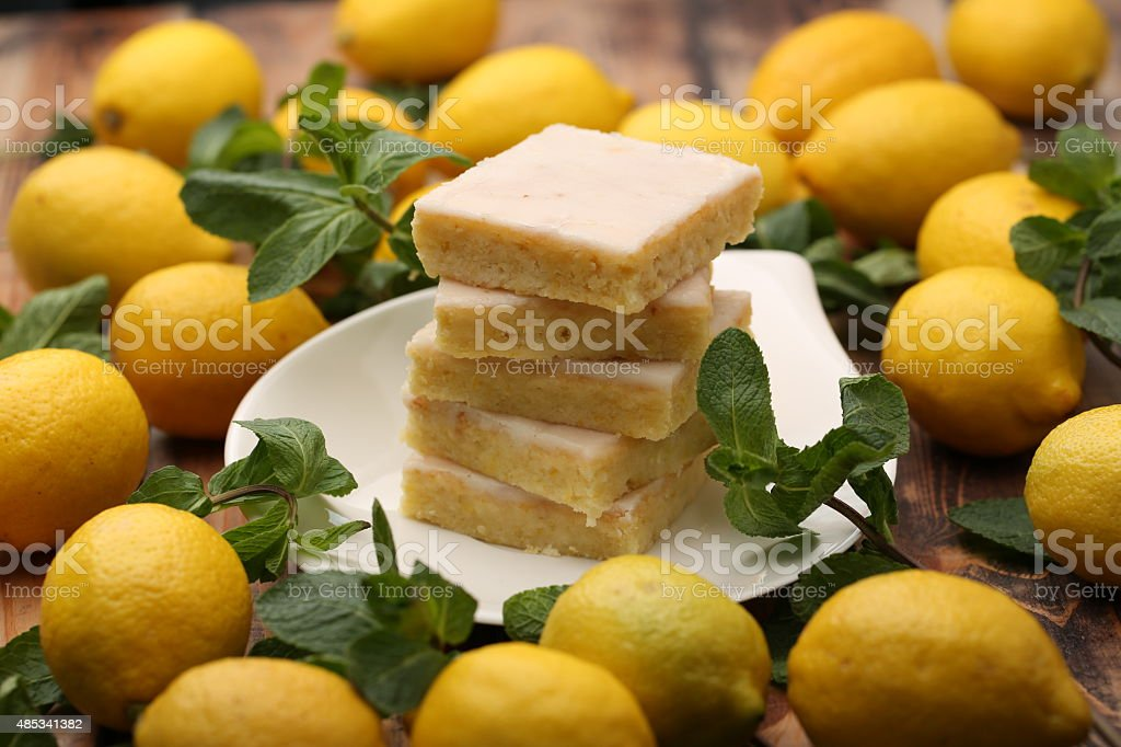 Cake and yellow lemons on wooden board stock photo
