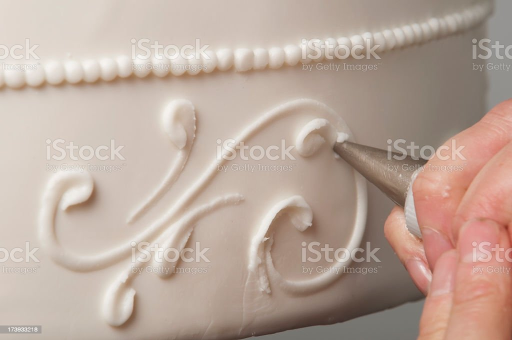 Cake decorator adding white swirls to wedding cake stock photo