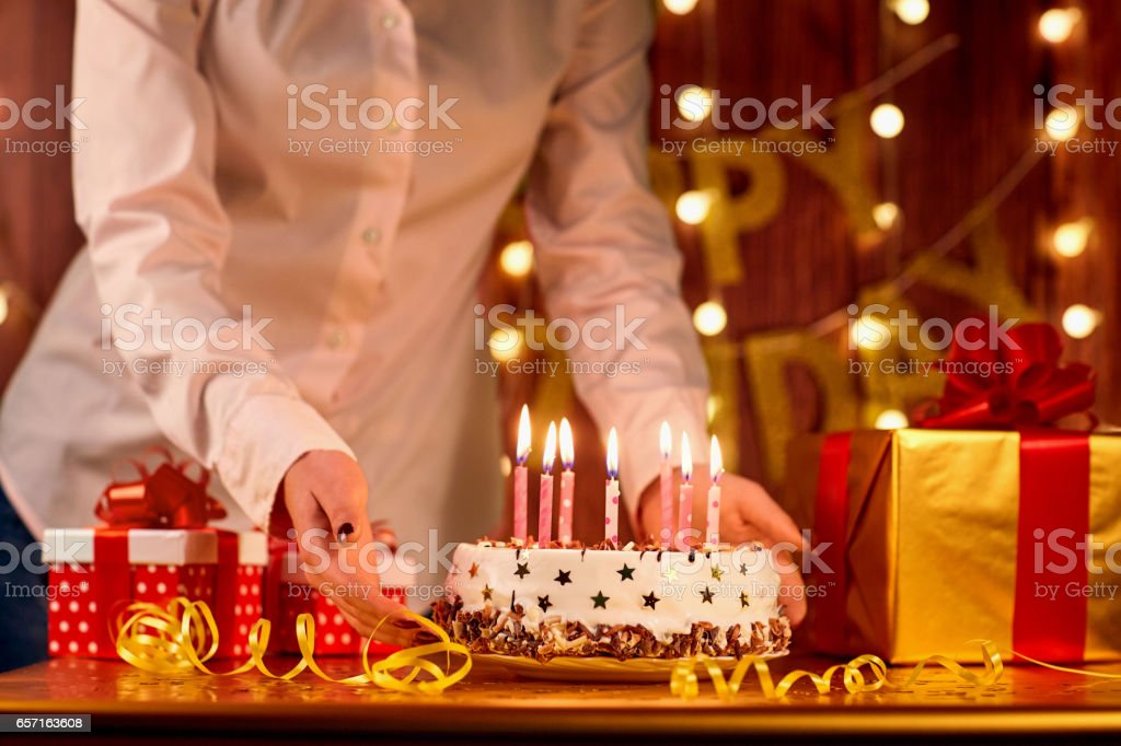 Cake Happy Birthday with candles and hand of the girl on  backgr stock photo