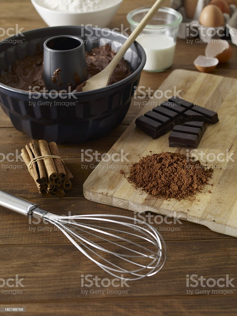 Cake ingredients in black mixing bowl with whisk and board stock photo