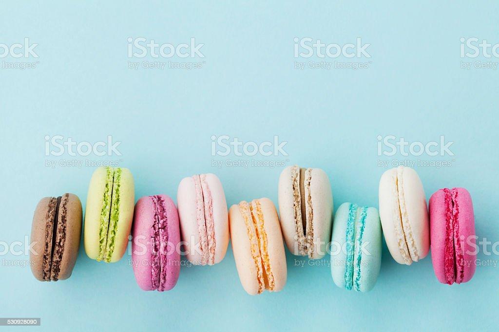 Cake macaron or macaroon on turquoise background, pastel colors stock photo