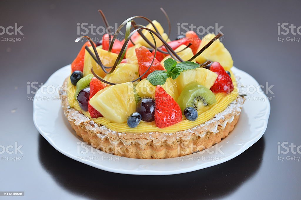 Cake of fruit with strawberry pineapple grape kiwi on white stock photo