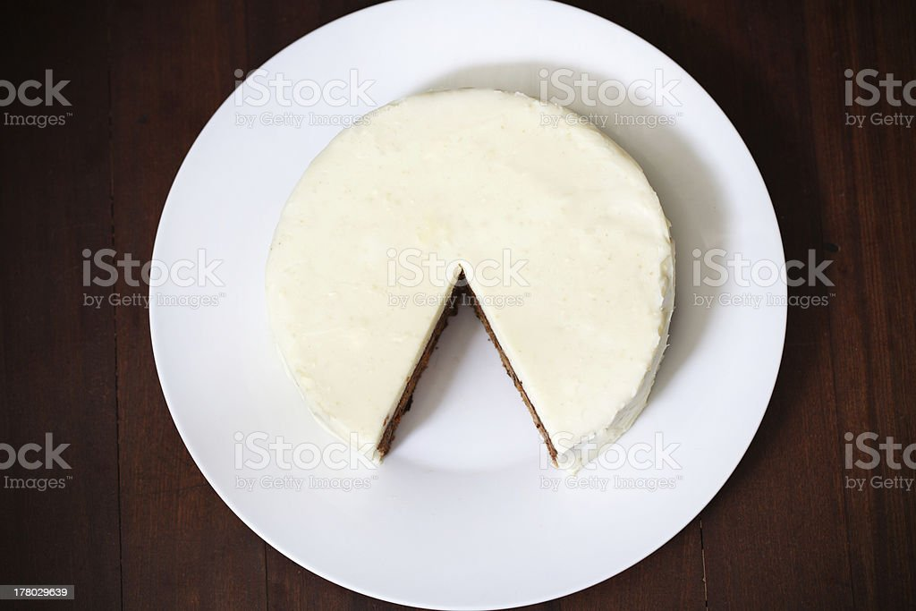 Cake with cream cheese icing, cut and piece missing royalty-free stock photo