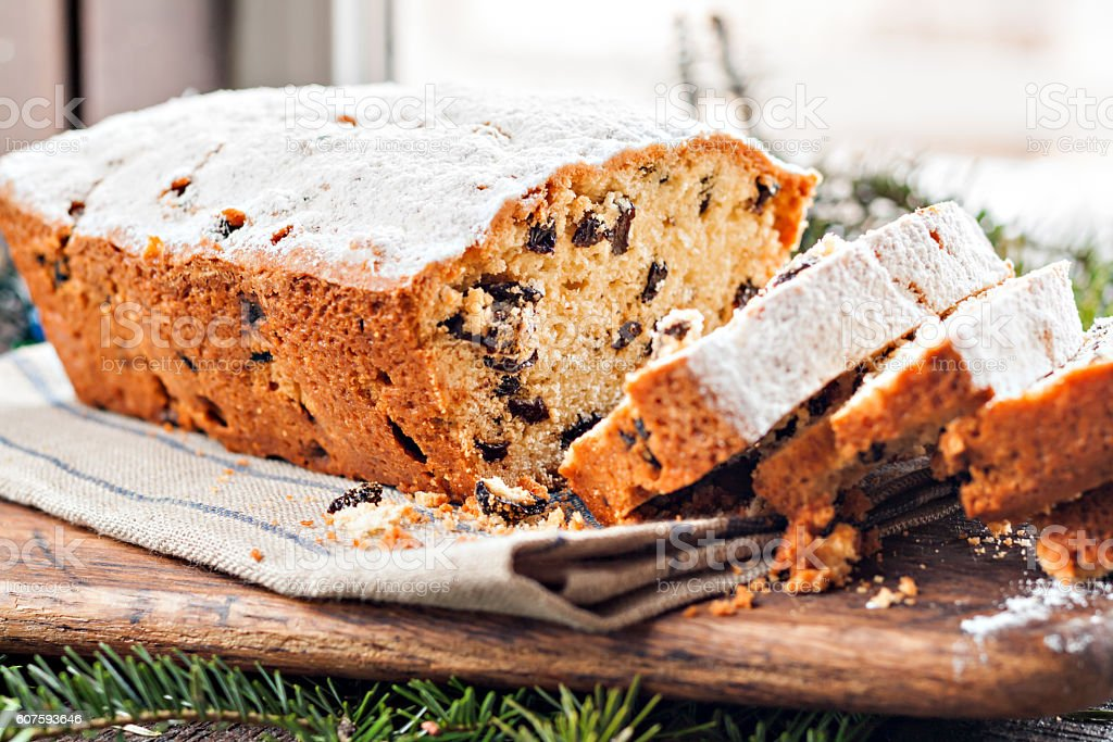 cake with raisins sprinkled with icing on a wooden table stock photo