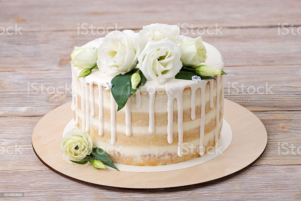 Cake with white glazing and white flowers stock photo