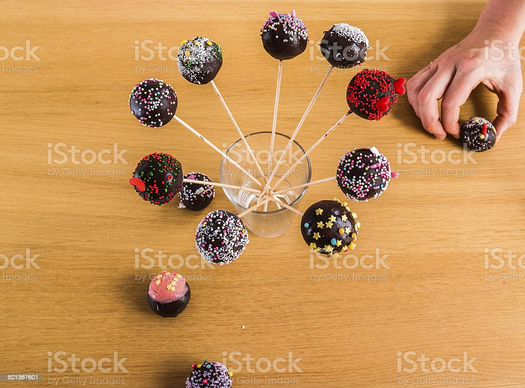cake-pops in stick in a glass with a helping hand stock photo
