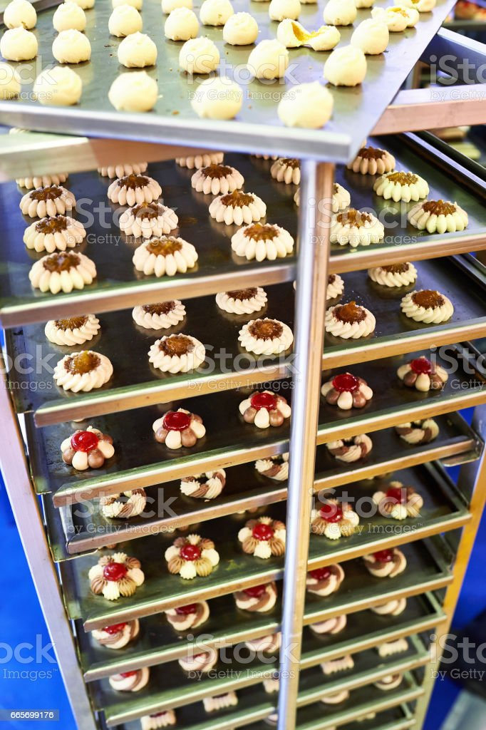 Cakes on metal shelves in confectionery factory stock photo