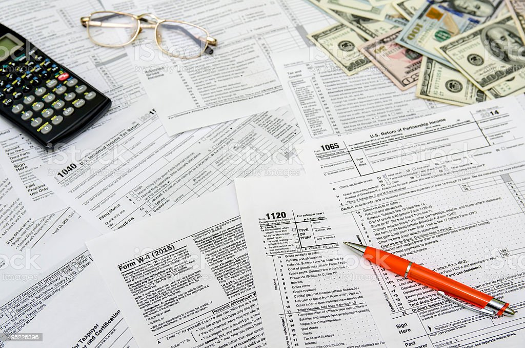 Calculating income tax return with money and pen stock photo