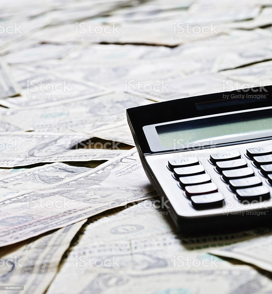 Calculator against dollar bill background: counting the cost or profit royalty-free stock photo