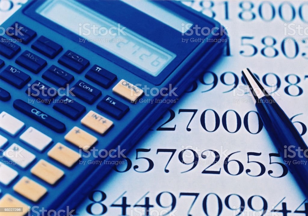 A calculator and a pen resting on a page of figures royalty-free stock photo
