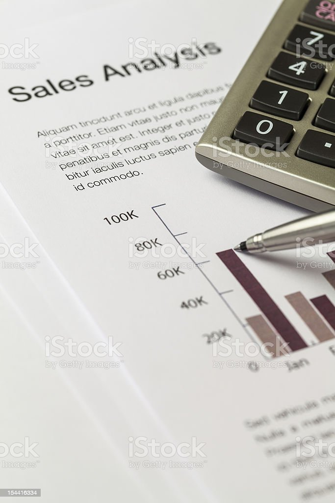 calculator and ballpoint pen on sales analysis document stock photo