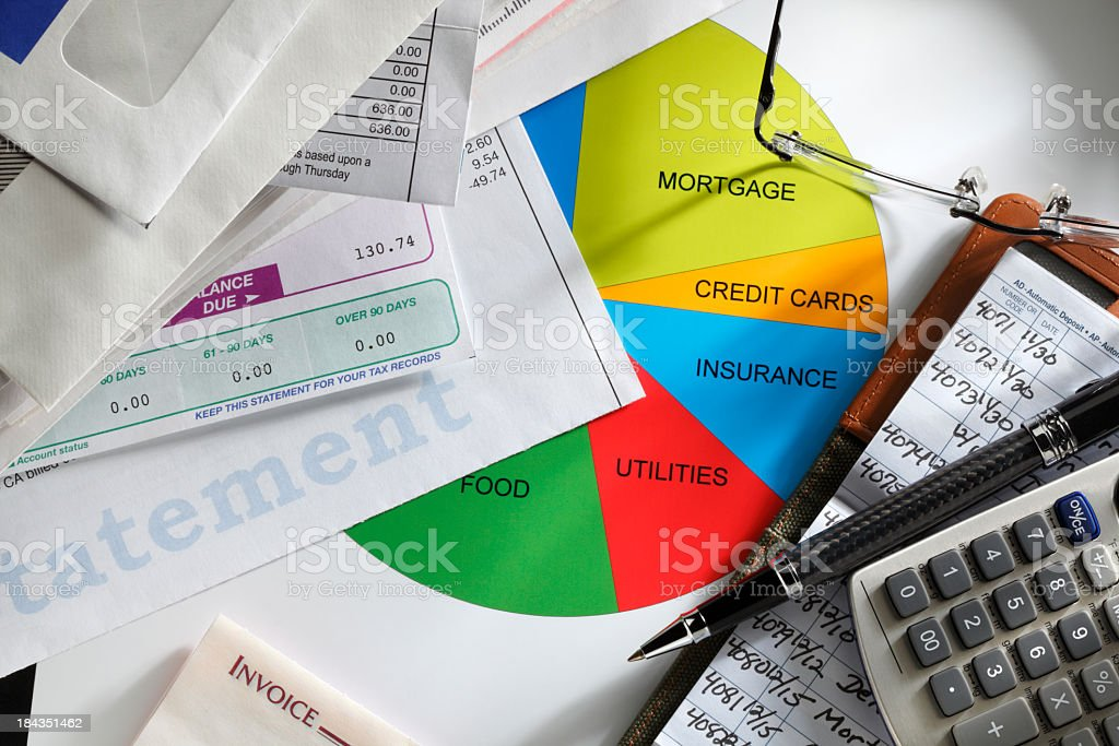 Calculator and checkbook next to a stack of monthly bills royalty-free stock photo