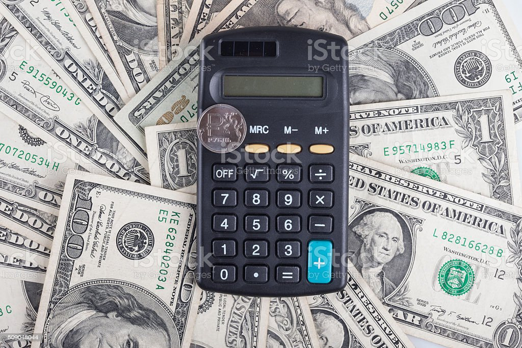 calculator and coin ruble on the background of banknotes dollars stock photo