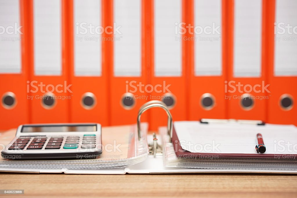 calculator and document on top  of open folder with documentation stock photo