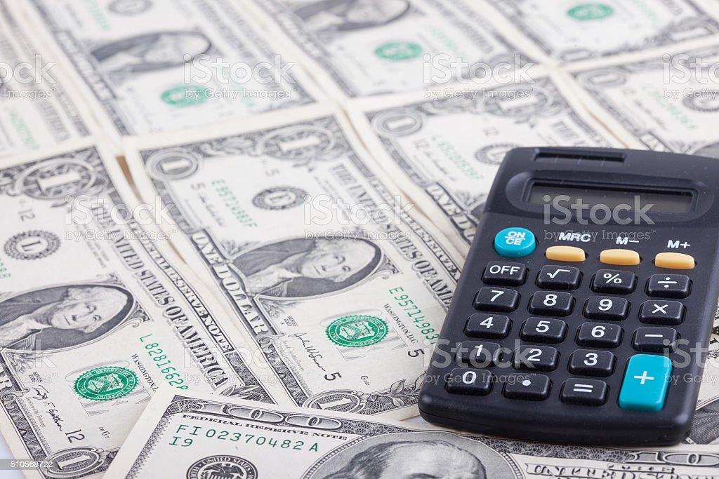 calculator and dollars as background metaphor stock photo