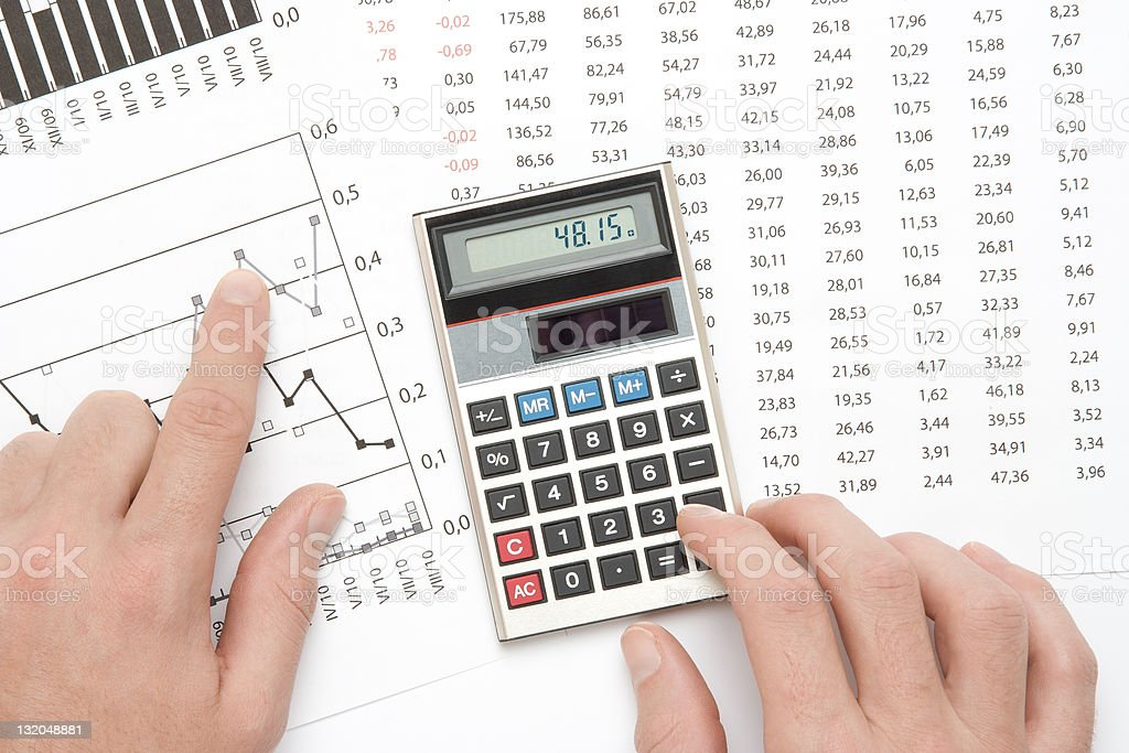 Calculator and finger pointing to graph in business analysis stock photo