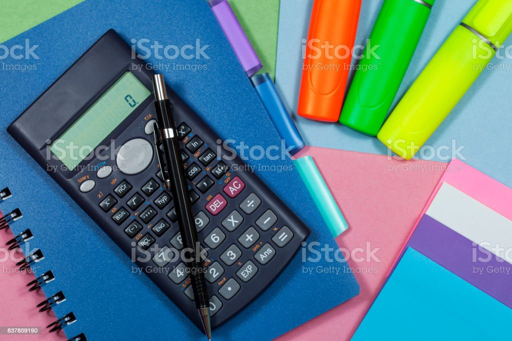 Calculator and highlighter pens with a note book stock photo