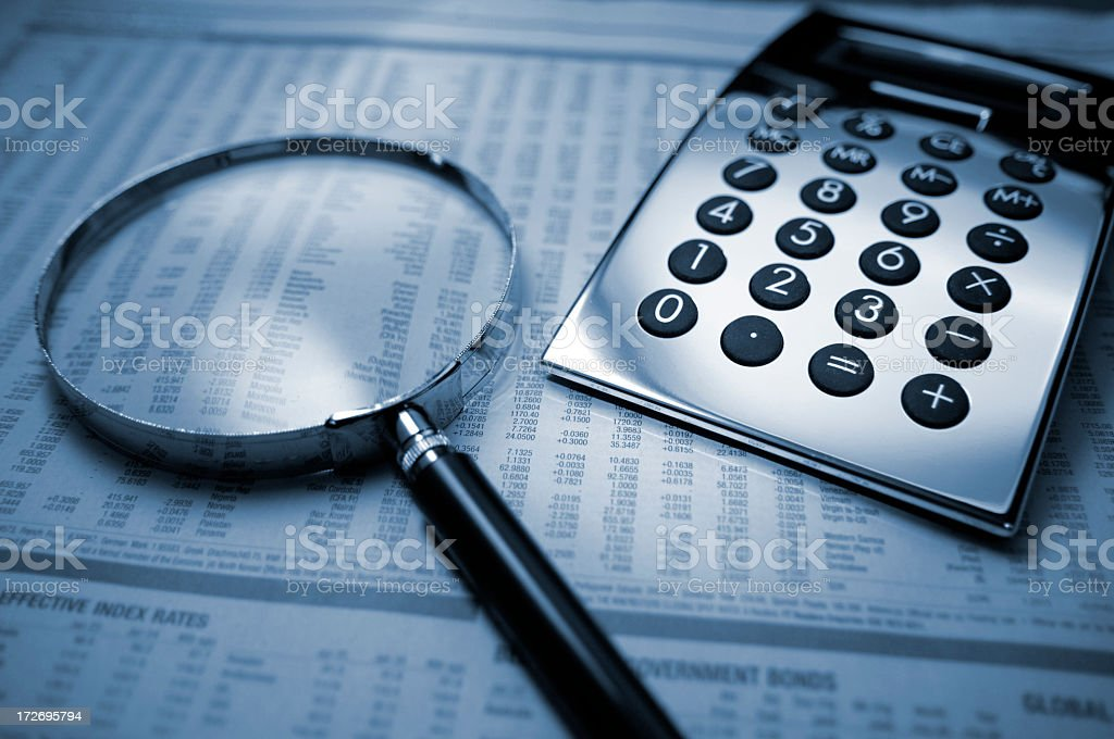 Calculator and Magnifying Glass on Financial Newspaper stock photo