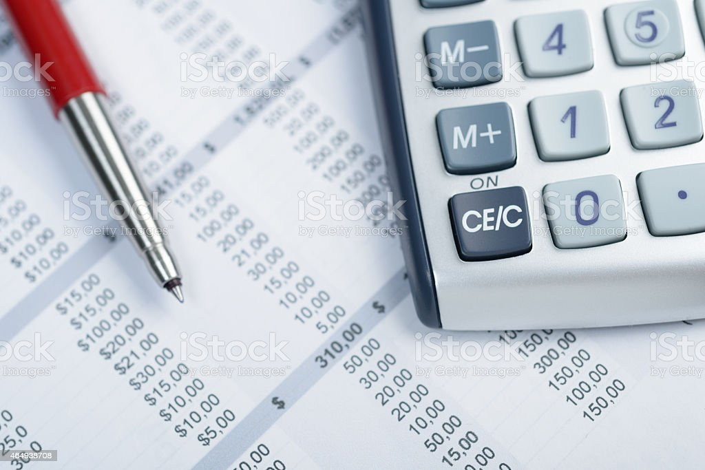 Calculator and pen on financial reports stock photo