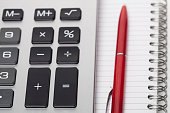 calculator and pen on note pad