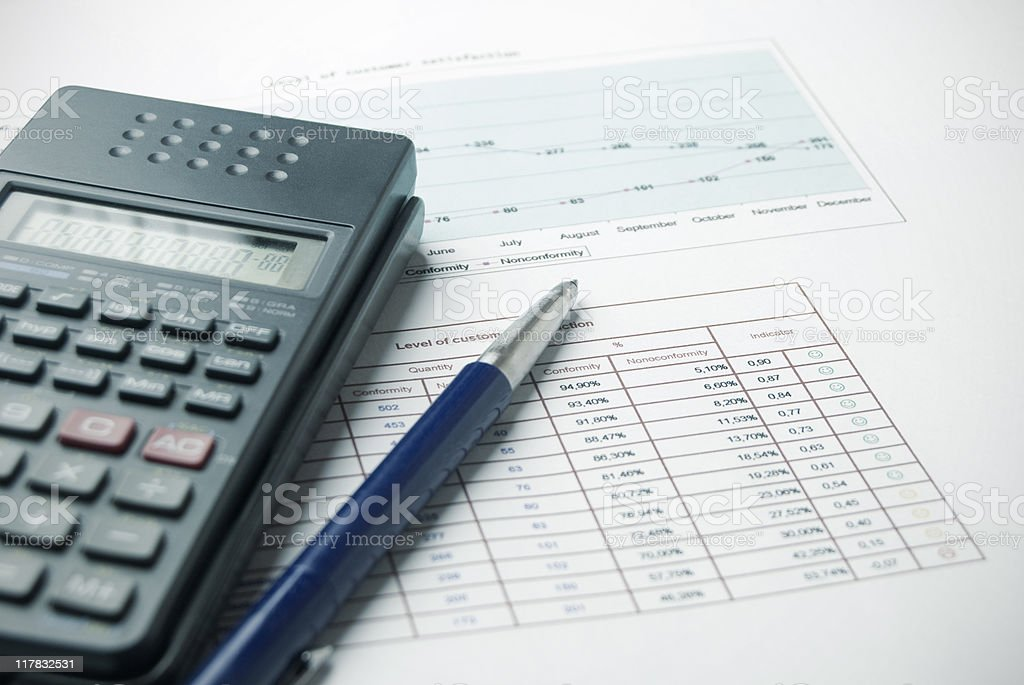 Calculator and pen on top of paper document of data royalty-free stock photo