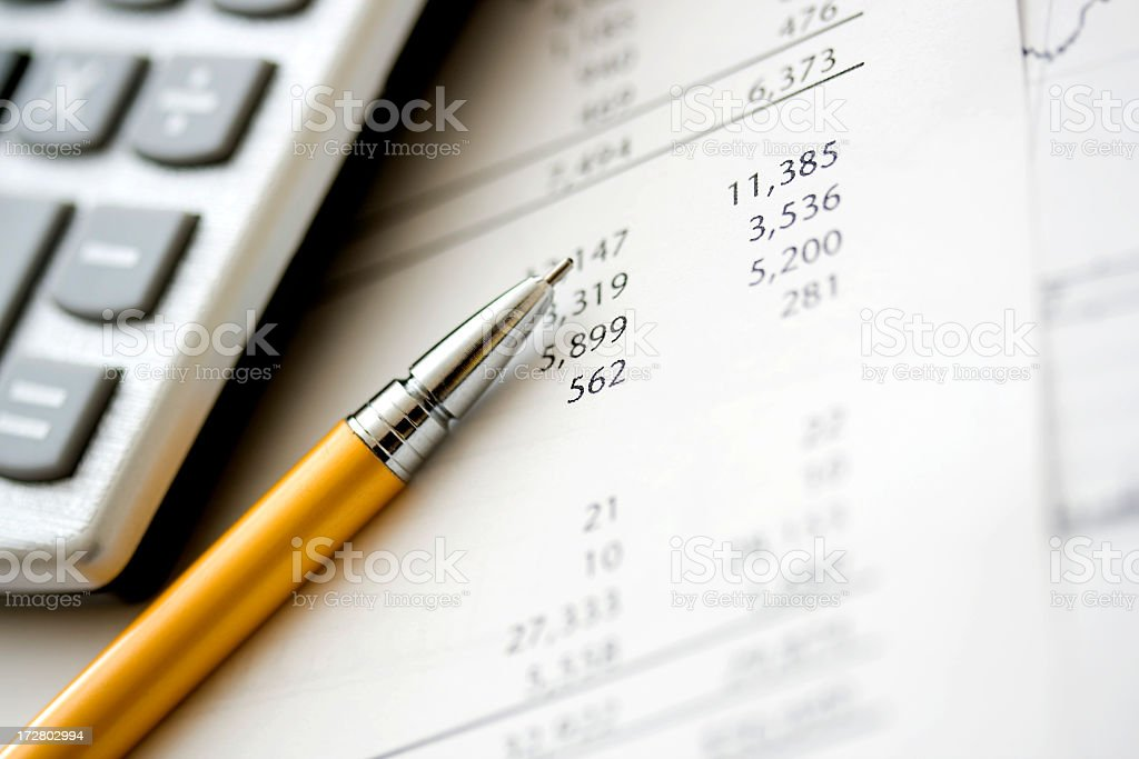 Calculator and pen over financial data royalty-free stock photo