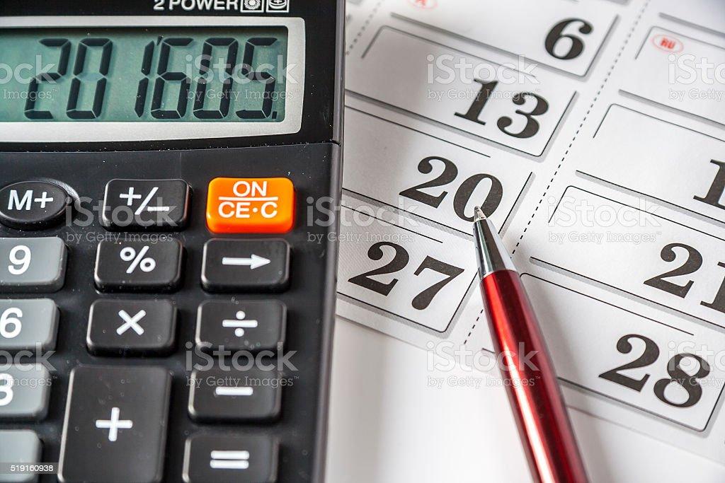 Calculator And Pen Resting On An Calendar stock photo