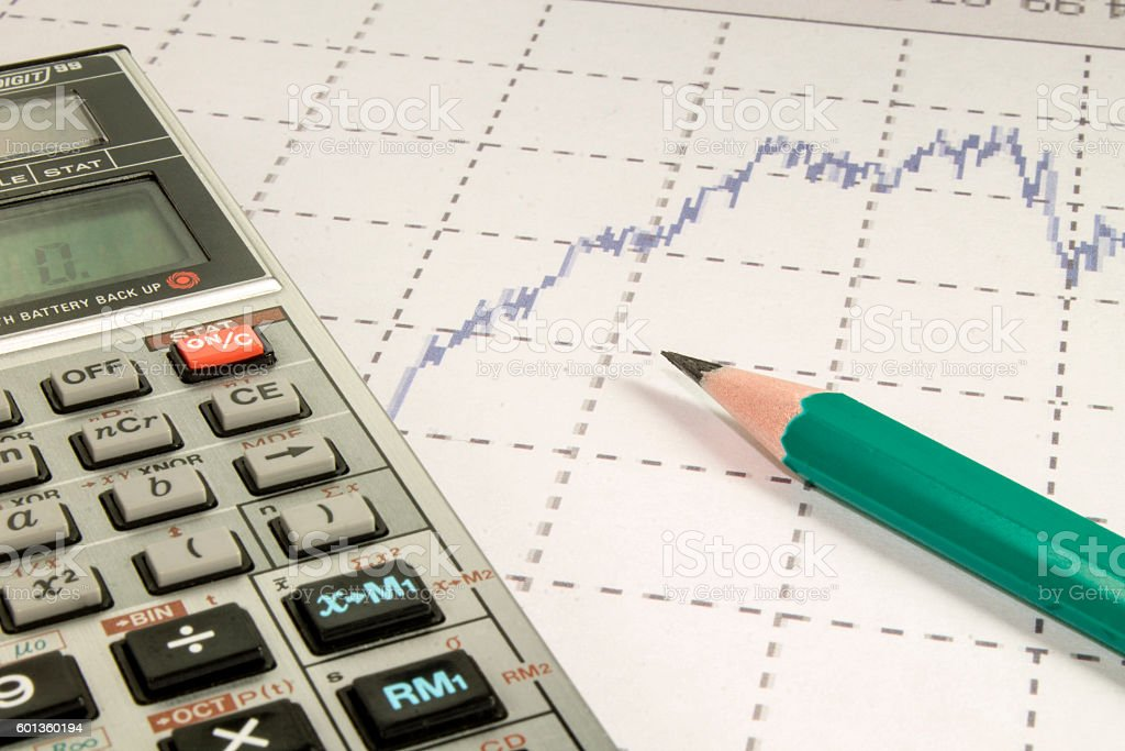 calculator and pencil  coins on graffica the Dow Jones stock photo