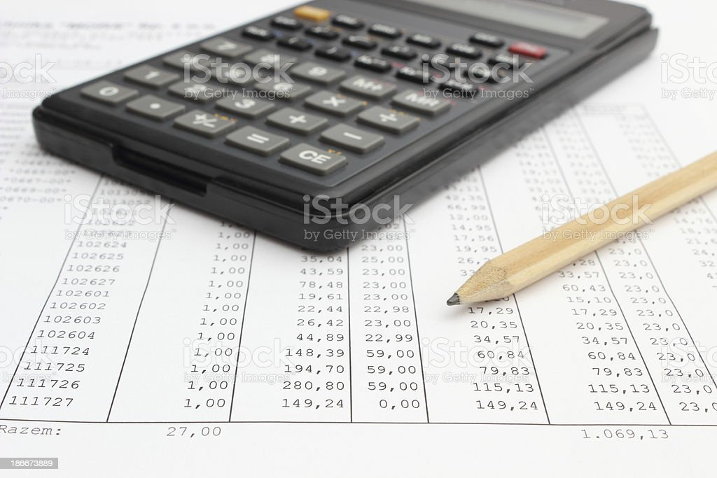 Calculator and pencil lying on spreadsheet royalty-free stock photo