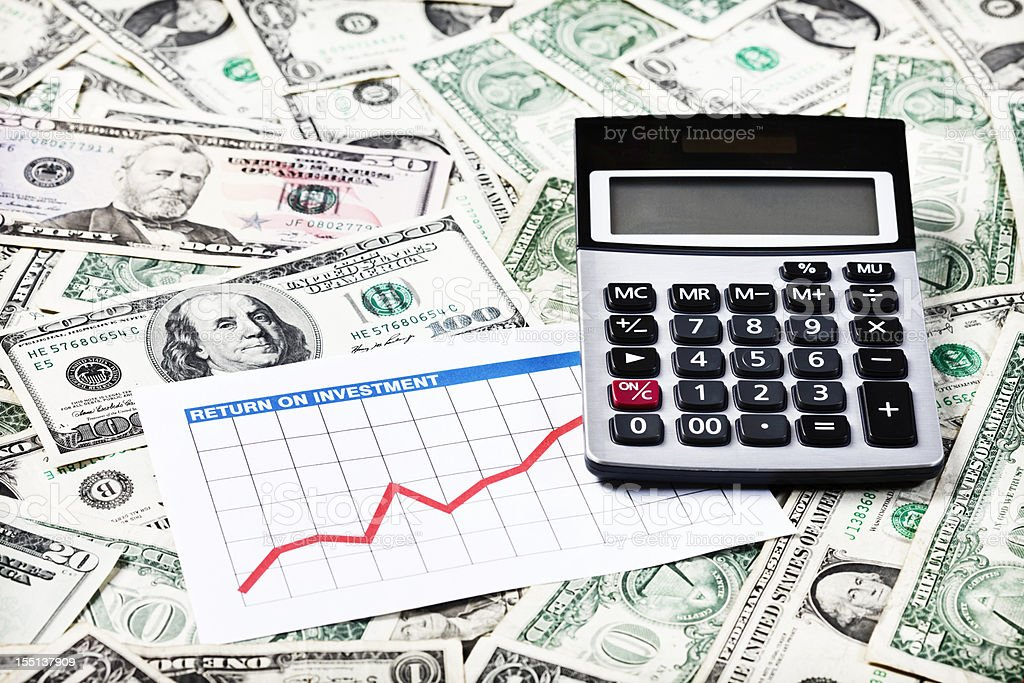 Calculator and rising graph on background of many US dollars royalty-free stock photo