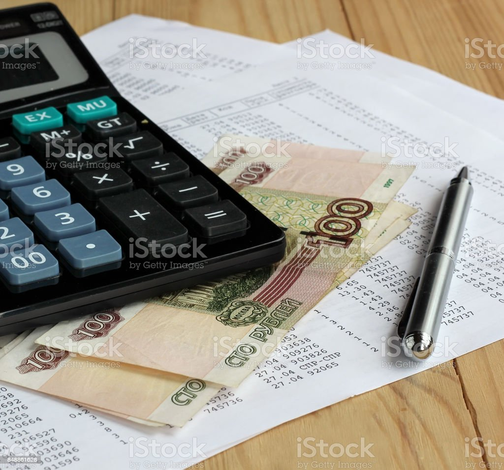 Calculator and Russian money on sheets of paper with numbers. stock photo