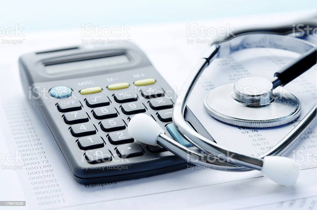 A calculator beside a stethoscope on top of paperwork stock photo