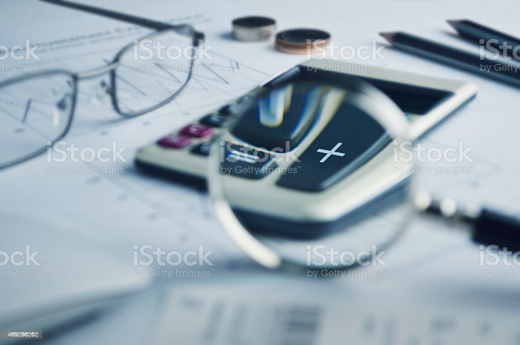 Calculator button plus and magnifying glass on graph paper stock photo