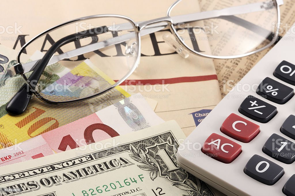 Calculator, glasses and currencies on a newspaper royalty-free stock photo