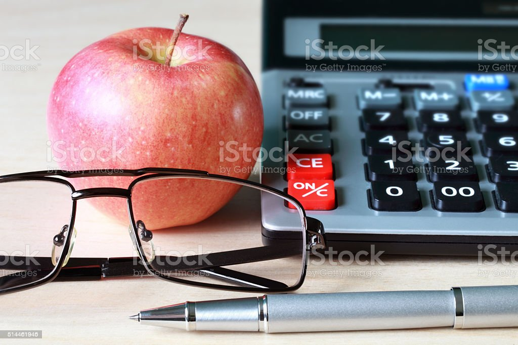 Calculator, glasses, pen and apple stock photo