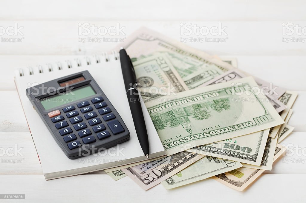 Calculator, notebook, pen and dollars cash money, finance concept stock photo