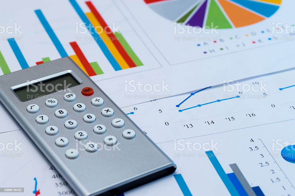 Calculator on colorful graphs and charts stock photo