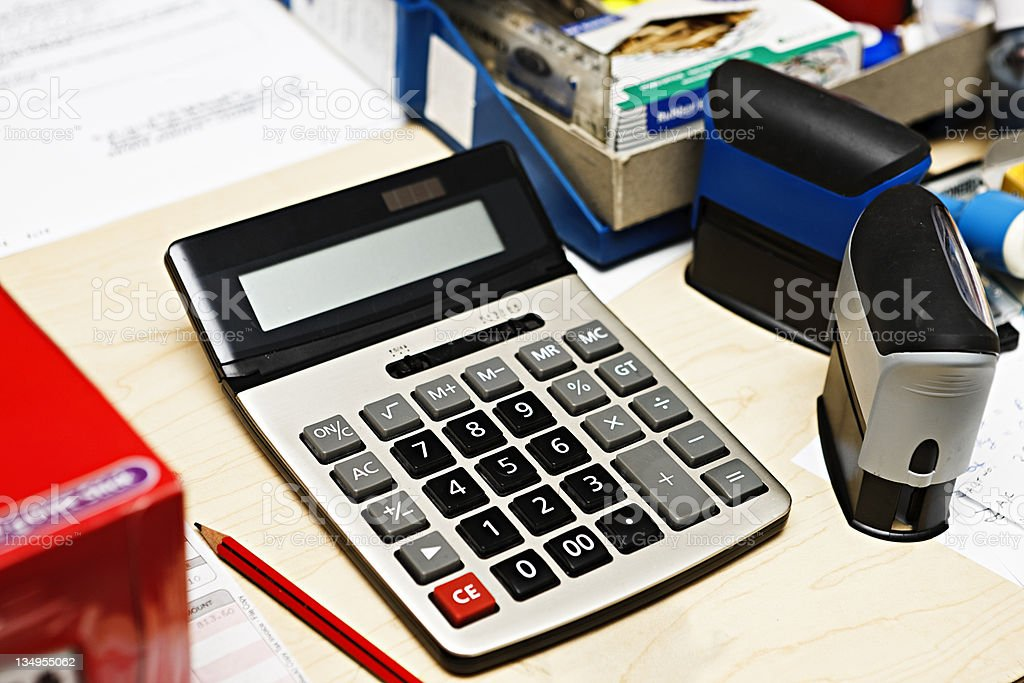 Calculator on desk with stamps and other office equipment stock photo