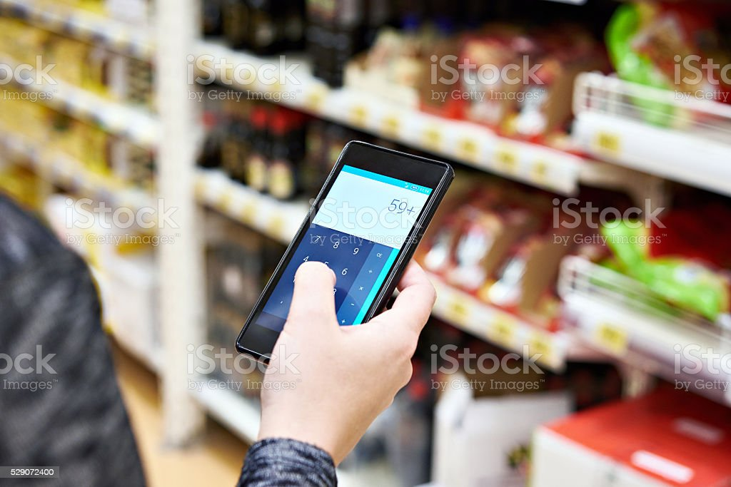 Calculator on smartphone screen in hand of women customers stock photo