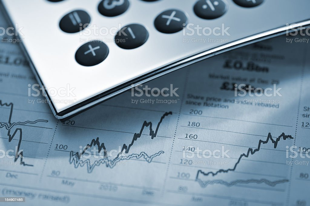 calculator on stock price graphs from financial newspaper royalty-free stock photo