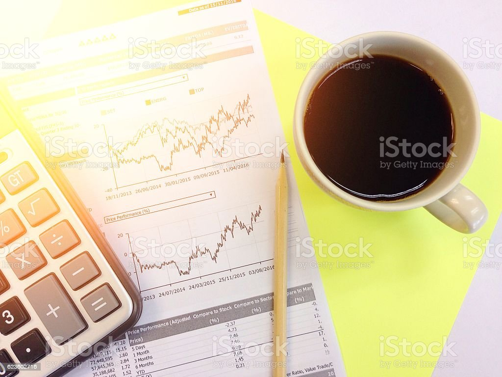 Calculator, pencil, coffee and data charts on yellow background stock photo