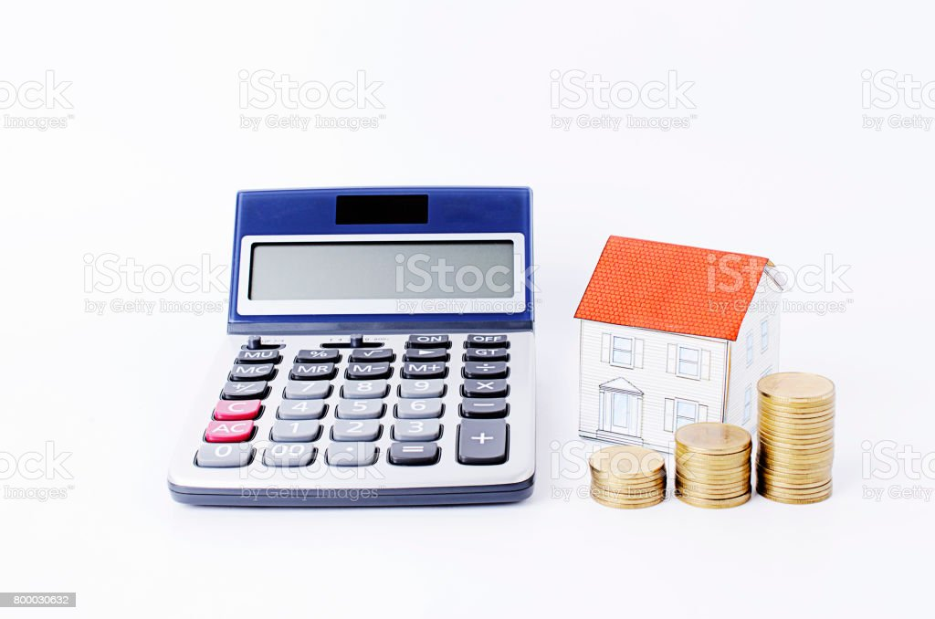 Calculator with paper house and coins stack on white backgrounds stock photo