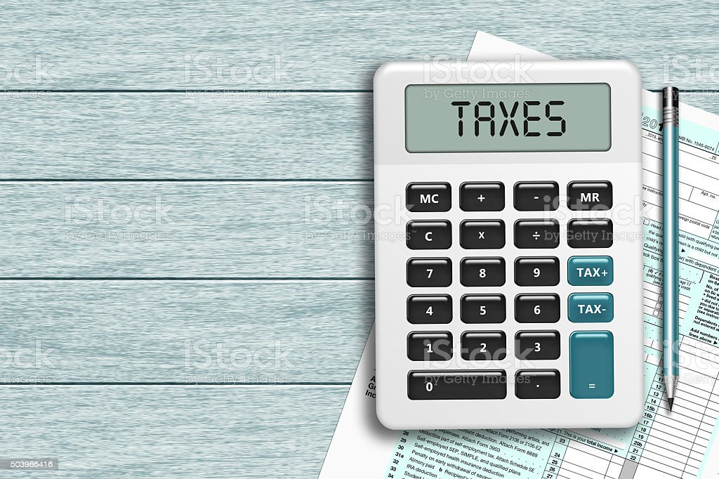 calculator with taxes text  and 1040 tax form on desk stock photo