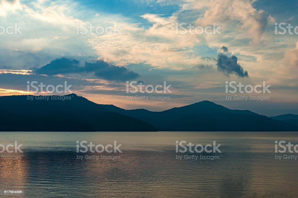 Caldera lake on dusk with mountain silhouettes on the background stock photo