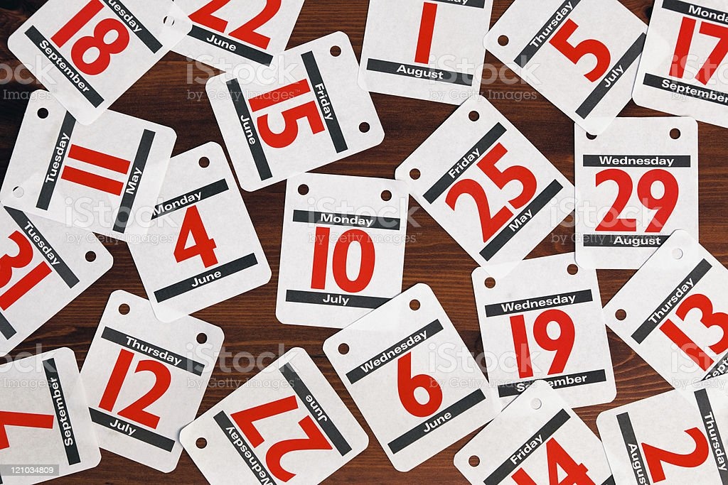 Calendar dates spread out on a wooden desk. royalty-free stock photo