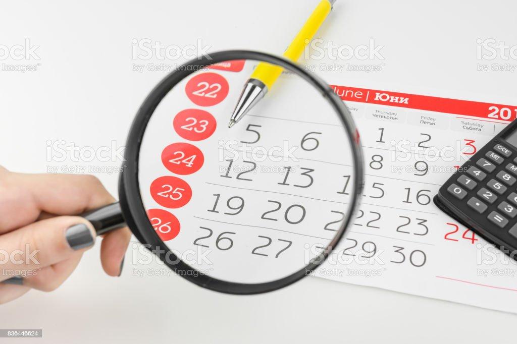 Calendar Days Looking Through Magnifying Glass stock photo