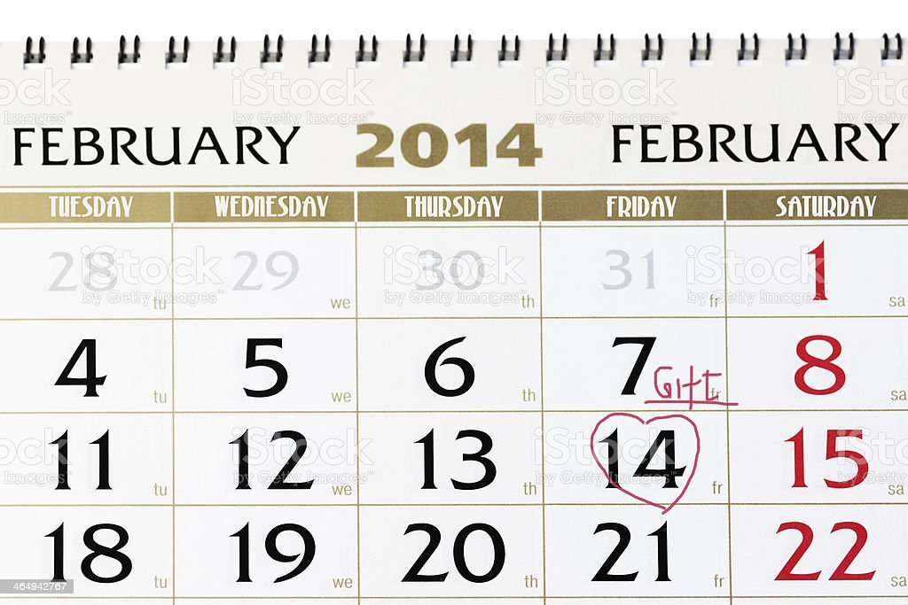 Calendar page with red heart on February 14 2014. stock photo