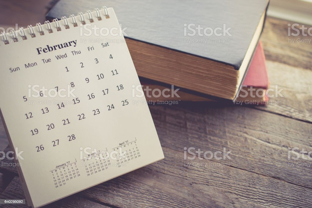 Calendar with the Book on Wooden Background in Vintage Tone stock photo